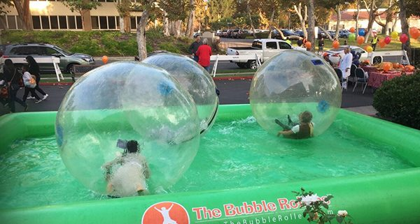 Calvary Chapel Carnival Kids enjoy Bubble Rollers at carnival. Kids playing inside plastic bubbles in pool of water.