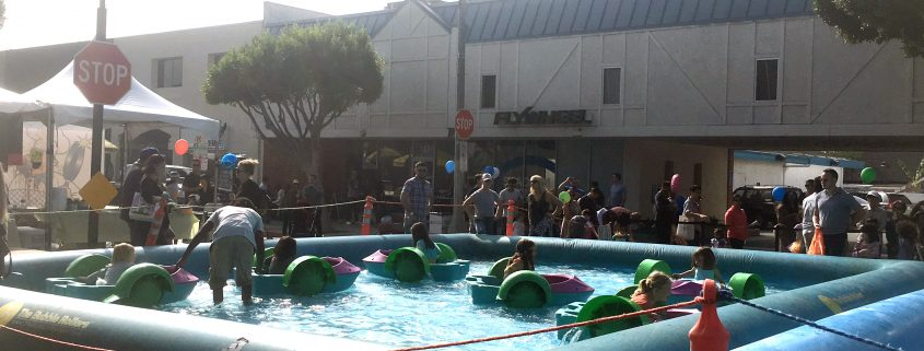 kids riding paddle rollers in an inflatable pool in the city of larchmont