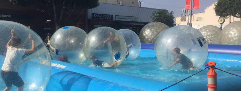 Kids rolling around in Bubble Rollers in the city of Larchmont. The bubble rollers are large plastic bubbles placed in a large pool of water.