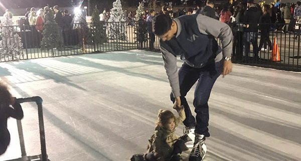 families skating on a fake ice skating rink rental