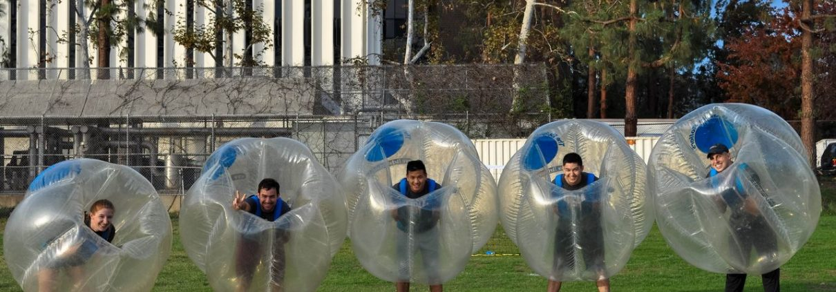 6 kids lined up in a straight line getting ready to play bubble soccer using bubble soccer rentals provided by The Bubble Rollers and Emerald Events