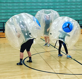 Three teenagers playing in plastic bubble balls. Hitting each other using kids party rental services provided by Emerald Events