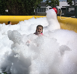 Little girl in a large pool of bubbles. Emerald Events brings the foam to any party, school, public, church event. Foam party rentals in Los Angeles, Orange County and Inland Empire Ca.
