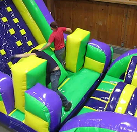 Two boys running through a large inflatable obstacle course rental. Emerald Events rents a variety of obstacle courses for birthday party, church, and public events