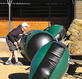 Man playing a fun game of task force laser tag rental. Hiding behind large bean bags. Laser Tag rentals are fun for both kids and adult parties