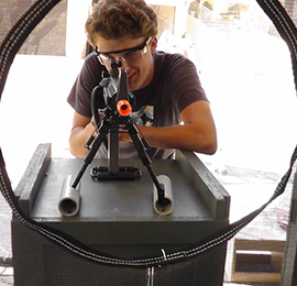 boy using a mobile shooting range rental equipment at a kids party