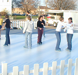 Adult skating on a mobile ice rink rental in the park in orange county, ca.