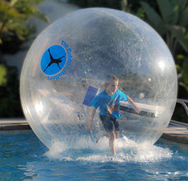Boy balancing inside a large plastic bubble on water. Kids party equipment rentals