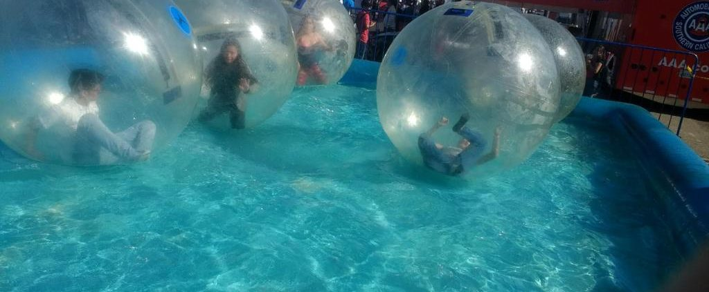 Kids rolling around in a large plastic ball in a pool. The Bubble Rollers Kids Party Rentals supplies the large balls at any event.